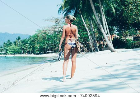 Young Woman With Longboard In Hand Walking On White Sand