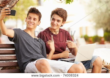 Two Teenage Boys Sitting On Bench Taking Selfie In Park