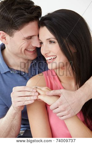 Studio Shot Of Man Putting Ring On Woman's Finger