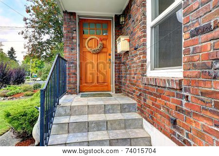 House With Brick Trim. Entrance Porch With Orange Door