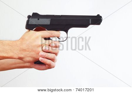 Hands with semi-automatic handgun on white background