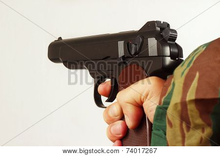 Hand in camouflage uniform with semi-automatic pistol