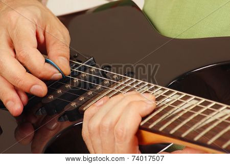 Artist put fingers for chords on electric guitar close up
