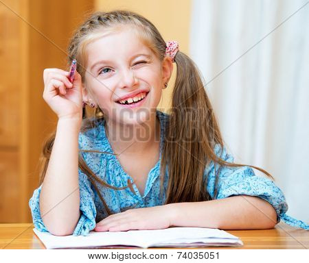 Cute dreamer little girl studying at home and smiling
