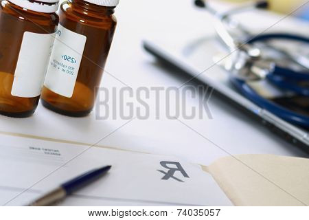 Laptop, stethoscope,bottle of pills, rx