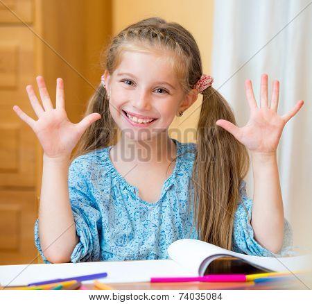Beautiful schoolgirl with hands up In Classroom