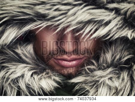 brutal face of man with beard bristles and hooded winter