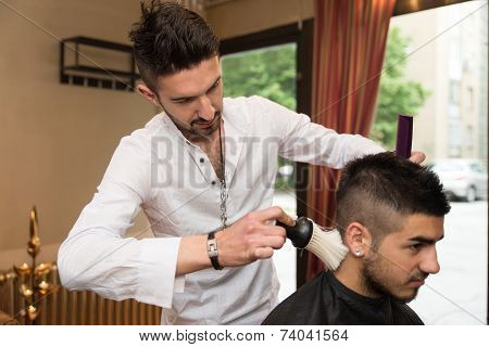 Hairdresser Making Haircut To Young Man