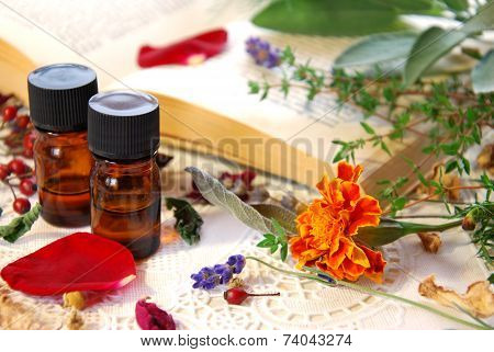 essential oils with herbs and book