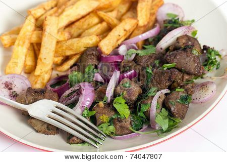 Albanian Liver, a traditional Turkish spiced lamb's liver recipe popular throughout the Middle East, with french fried potato chips and a fork.