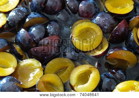 Poached cutted plums in sugar syrup