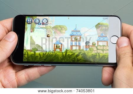 Hands Playing Angry Birds Game On Apple Iphone6