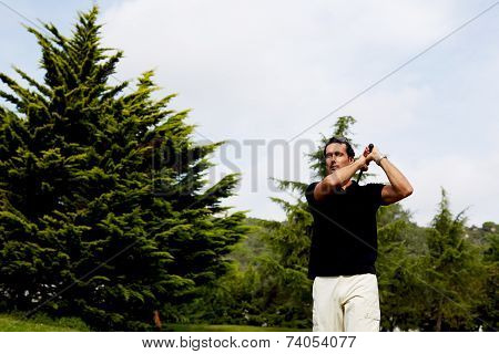 Professional golf player in action hitting golf ball