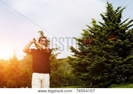 Confident golfer swinging his driver and looking away
