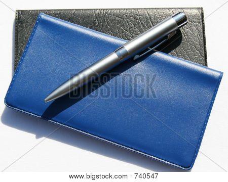 Blue Checkbook Over Black Checkbook With Pen