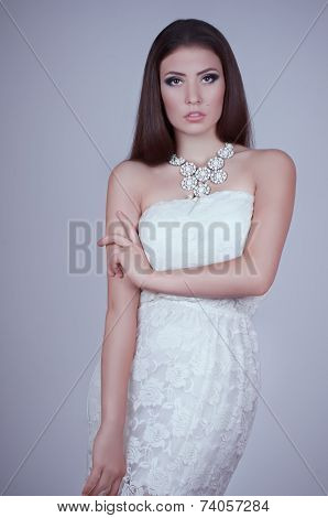 Fashionable young girl in white dress. Studio shot