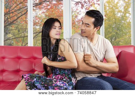 Hispanic Couple Quarreling On Sofa