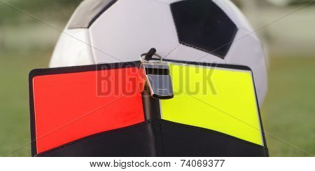 Football referee red and yellow card, whistle and ball.  Rules of the game concept image