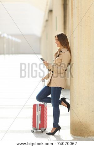 Traveler Woman Texting A Smartphone While Is Waiting With A Suitcase