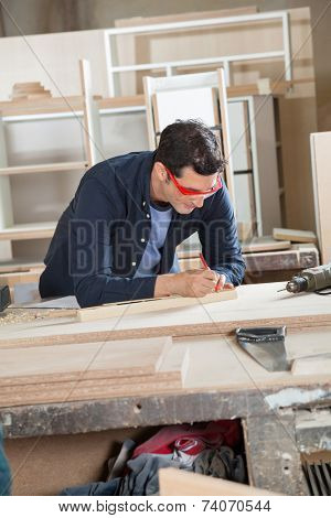 Young carpenter measuring wood at workbench in workshop