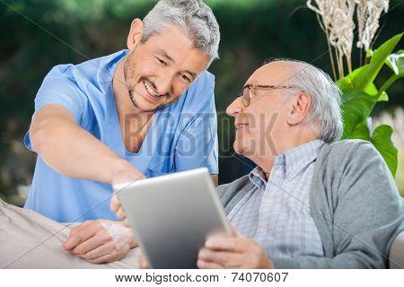 Smiling male nurse assisting senior man in using tablet PC at nursing home porch