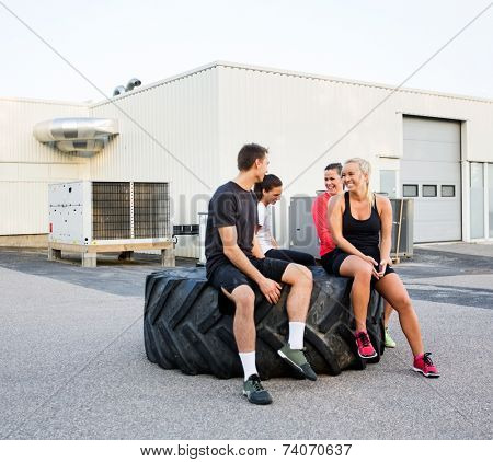 Group of fit friends conversing while relaxing on tire after workout outdoors