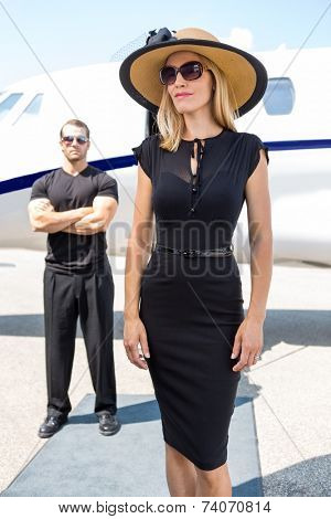 Beautiful woman in elegant dress with bodyguard and private jet in background