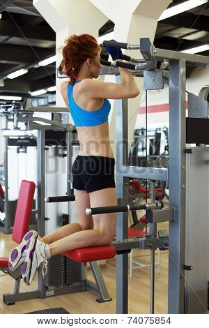 View of young redhead girl exercising on simulator
