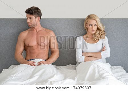 Married couple having an argument sitting up n their bed facing off in opposite directions as they ignore one another