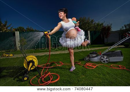 Beautiful pregnant woman having fun with garden hose splashing summer rain.