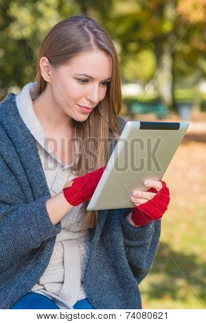 Close up Smiling Young Woman in Autumn Outfit Busy Browsing with her Apple Ipad. Captured Outdoor.