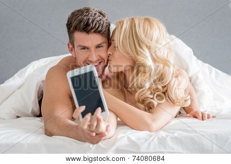 Young Caucasian Couple on Bed Taking Sweet Photos while Kissing.