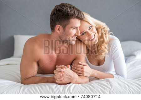 Happy attractive couple relaxing on their bed in the sun shining through the window cuddling and smiling happily at the camera