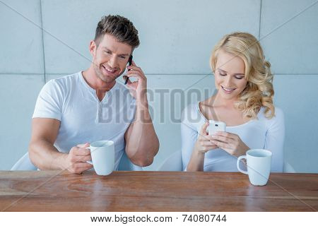 Young couple each using their mobile phone as they sit drinking their morning coffee with the husband making a call and the wife texting a message