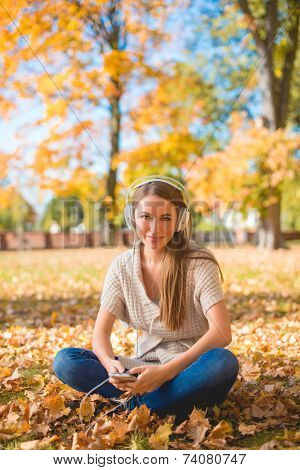 Pretty Young Woman Sitting on Grassy Ground with Dried Leaves  Listening Music on Ipod with Headset. Looking at Camera. Isolated on Nature Background.