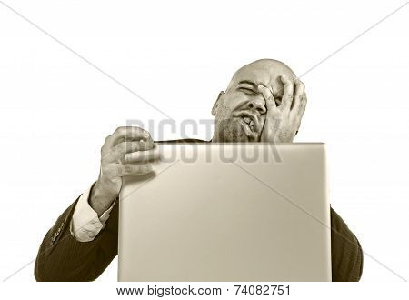 Businessman In Crisis And Stress At Computer Laptop Holding Monitor