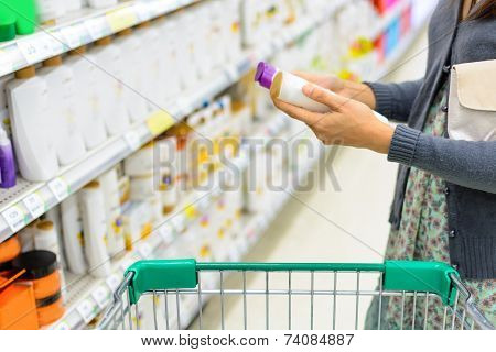 Girl Comparing In Supermarket