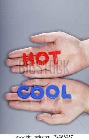Man holding plastic letters spelling HOT and COOL in his hands.