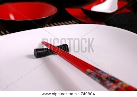 Red chopsticks on white plate