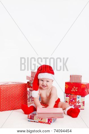 Santa child with gift box near Christmas tree at home