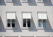 foto of awning  - Three windows on grey building with white awnings and shadow - JPG