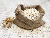picture of oats  - Small burlap sack with oat on a wooden background - JPG
