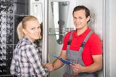 stock photo of plumber  - Young woman and plumber are looking at the camera while standing in the bathroom - JPG