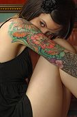 stock photo of coy  - Photo of a shy young female with colourful tattoos - JPG