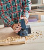stock photo of workbench  - Midsection of carpenter working with electric planer on wooden plank at workbench - JPG