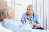 picture of male nurses  - Male caretaker explaining prescription to senior man in bedroom at nursing home - JPG