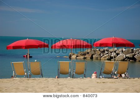 deckchairs with sunshades on the beach in italy