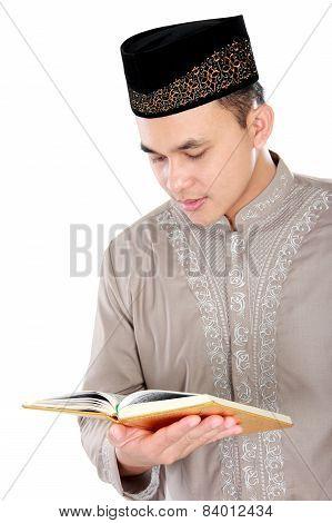 Young Muslim Man Reading A Quran