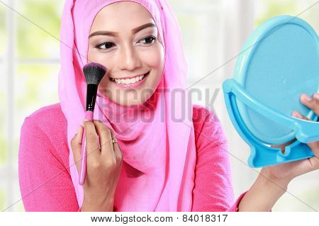 Cheerful Young Woman Looking At The Mirror While Applying Blush