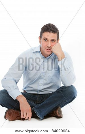 Tired Man Sitting On The Floor Leaning On His Hand